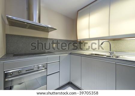 modern designer kitchen with silver cupboards and granite worktop - stock photo