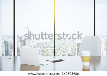Modern desk in an office with a window and a view of the city - stock photo