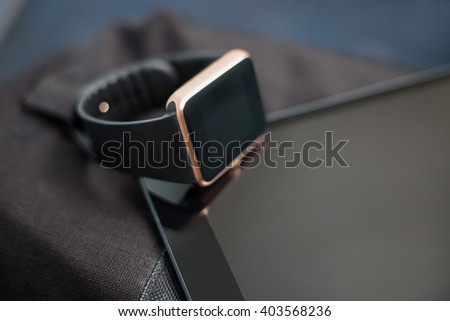 Modern digital accessory - fashionable smart wrist watch on tablet pc and travel bag. This gadgets let you always stay connected to social media, email and internet. Horizontal orientation - stock photo