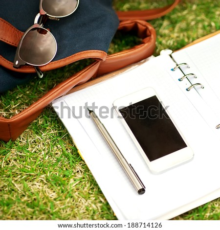 Modern digital notebook  with mobile smartphone on green grass - stock photo