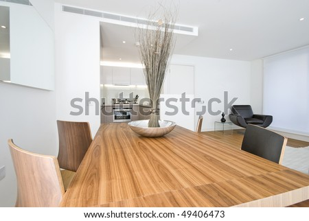 Modern dining area with wooden table, designer chairs and kitchen in a backround