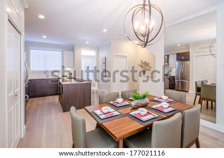 Modern dining room interior with a kitchen, table, and mirror