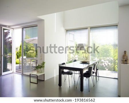 modern dining room interior with view to garden - stock photo