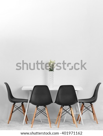 Modern dining room. White table with bouquet of flowers and black chairs - stock photo