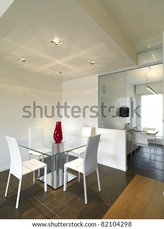 modern dining room with sight to white kitchen and wood floor