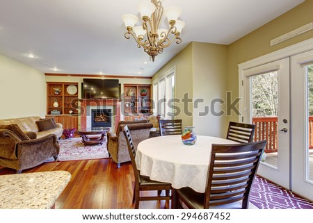 Modern dinning area with hardwood floor and connected living room.