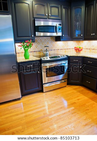 Modern domestic kitchen with new appliances and wooden floor - stock photo