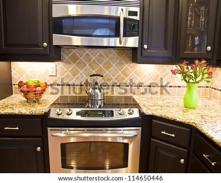 Modern domestic kitchen with steel oven and microwave - stock photo