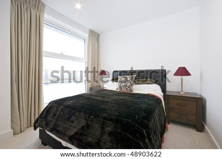 Modern double bedroom with king size bed and wooden bedside tables - stock photo