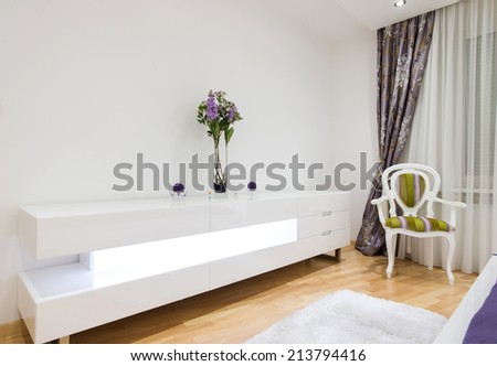 Modern dresser furniture and chair in home interior - stock photo