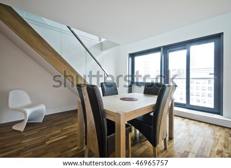 modern duplex apartment with hard wood furniture and staircase - stock photo