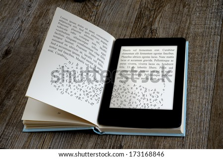 modern ebook reader on book on wooden background - stock photo