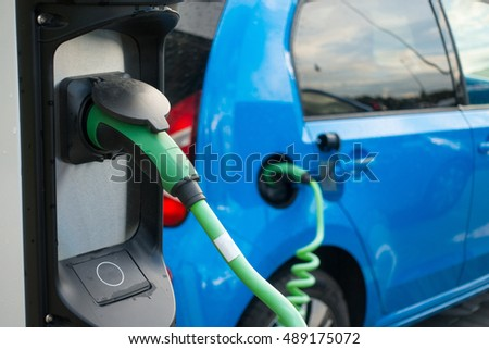 Modern electric car connected to charge station