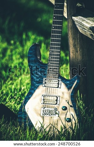Modern Electric Guitar at Countryside Place. Wooden Fence and Summer Grass. Country Music Theme. - stock photo