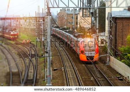 Modern electric locomotive pulling a high-speed train on rails. Technical railway station - operational locomotive depot on autumn morning. Transport infrastructure of railways, Russia