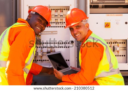modern electrical co-workers using laptop computer checking transformer - stock photo