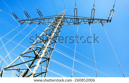 modern electricity pylon in front of blue sky