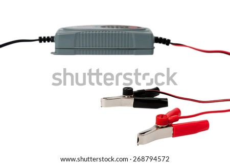 Modern electronic charger for car battery with jumper cables isolated on white background - stock photo