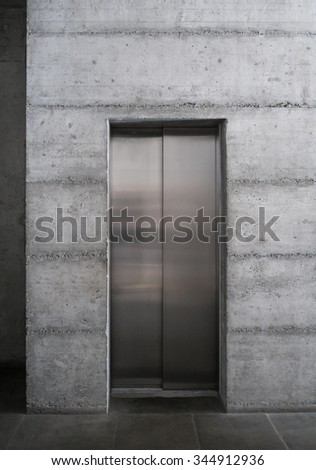 Modern elevator in a minimalist concrete building - stock photo