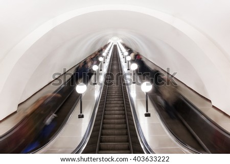 Modern escalator with blurred in motion people in Moscow metro, Russia. - stock photo