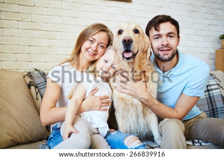Modern family and their cute pet resting at home