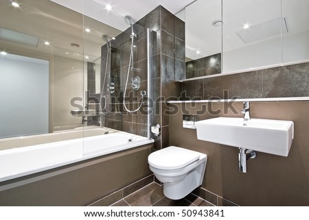 Modern family bathroom with large bath tub and natural stone tiled walls in brown