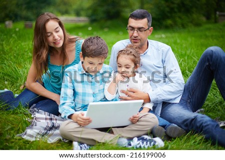 Modern family of four using laptop while resting in park - stock photo