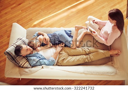 Modern family of three relaxing on sofa - stock photo