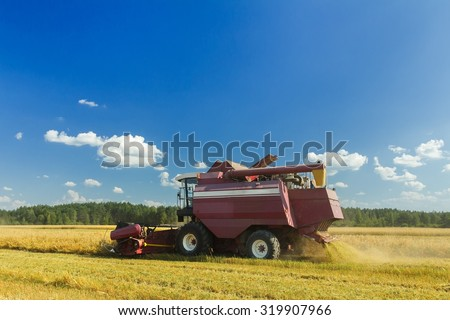 Modern farm combine harvester with elevator to upload cereal into the trailer   - stock photo