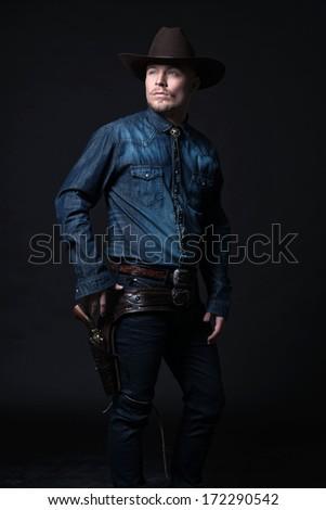 Modern fashion cowboy. Wearing brown hat and blue jeans shirt. Pulling his gun. Blonde hair and beard. Studio shot against black. - stock photo