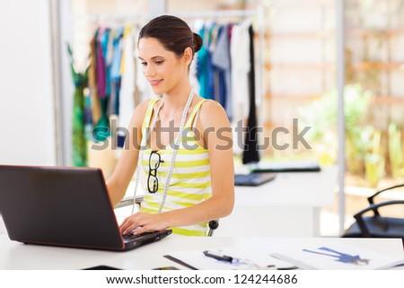 modern fashion designer sketching using laptop computer - stock photo