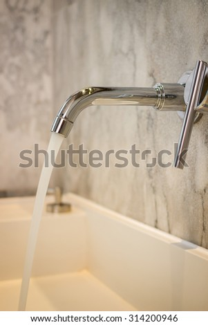 Modern faucet with running water - stock photo