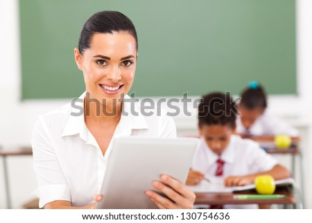 modern female school teacher using tablet computer in classroom