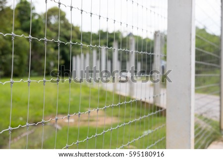Modern fence made of wire on concrete poles