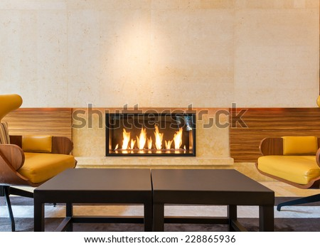 Modern fireplace sitting area with two leather chairs. Interior design. - stock photo