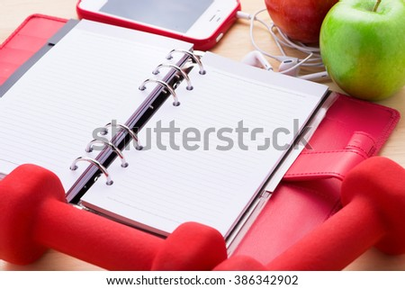 Modern fitness and gym workout concept. Healthy lifestyle background with blank copy space smartphone screen, dumbells, red apple close up. - stock photo