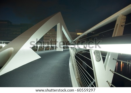 Modern footbridge over River Clyde in Glasgow, Scotland, UK, Europe. Shot from low angle at night to show illuminated handrail and geometric shapes. - stock photo