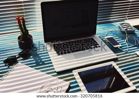 Modern freelance desktop with accessories and distance work tools, blank screen laptop computer and digital tablet, mouse, sunglasses, phone charging, touch pad and cactus plant, business workspace  - stock photo