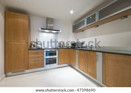 Modern fully fitted kitchen with appliances - stock photo