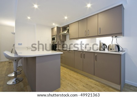 Modern fully fitted kitchen with appliances and bar seating in white - stock photo