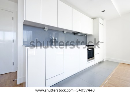 Modern fully fitted kitchen with kitchen appliances in white and gray - stock photo
