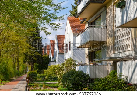 Modern german street with white stoned houses with tiled roofs. Sunny day and green alley.