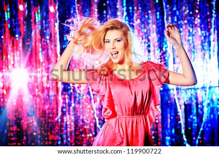 Modern girl dancing at the party. Disco lights.