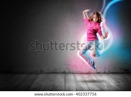Modern girl jumps and dances with glowing light lines following her move on dark background - stock photo