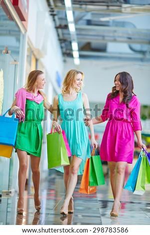 Modern girls with paperbags enjoying weekend shopping - stock photo