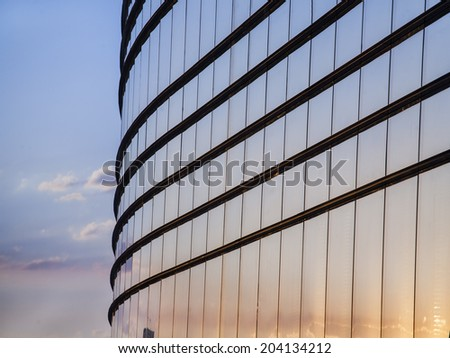 Modern glass building exterior with sky - stock photo