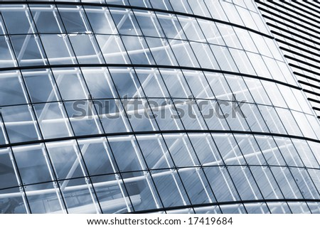 Modern glass business center's wall with dramatic sky reflections