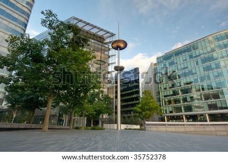modern glass office block under blue sky in more london by thames river, a new business district in london - stock photo