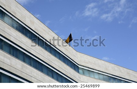 Modern glassed office building with flags outside - stock photo