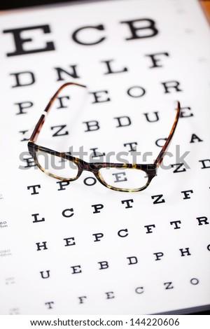 modern glasses lying on eye test chart - stock photo